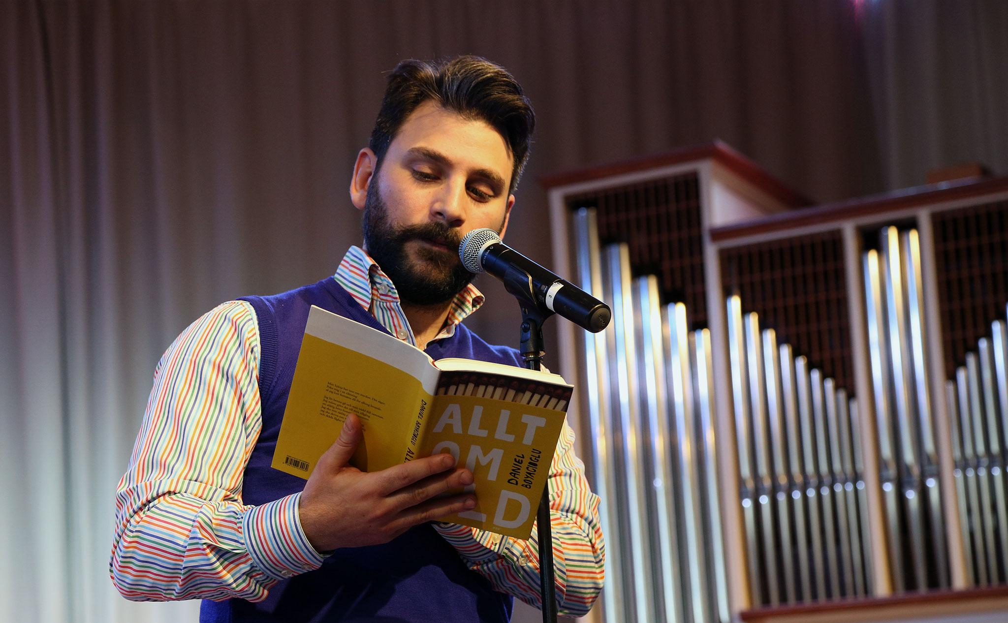"""Daniel står på scen i aulan och läser ur en gul bok med texten """"Allt om eld""""."""