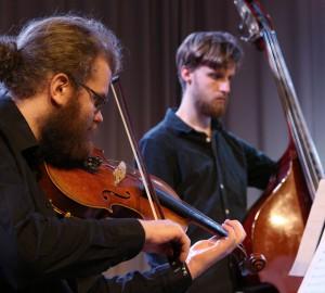 Deltagare i förgrunden spelar fiol, i bakgrunden syns en kontrabasist.