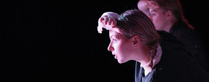 Foto från en dansföreställning. Kristin i profil spejar åt vänster i bild, med ena handen skuggar hon ögonen.