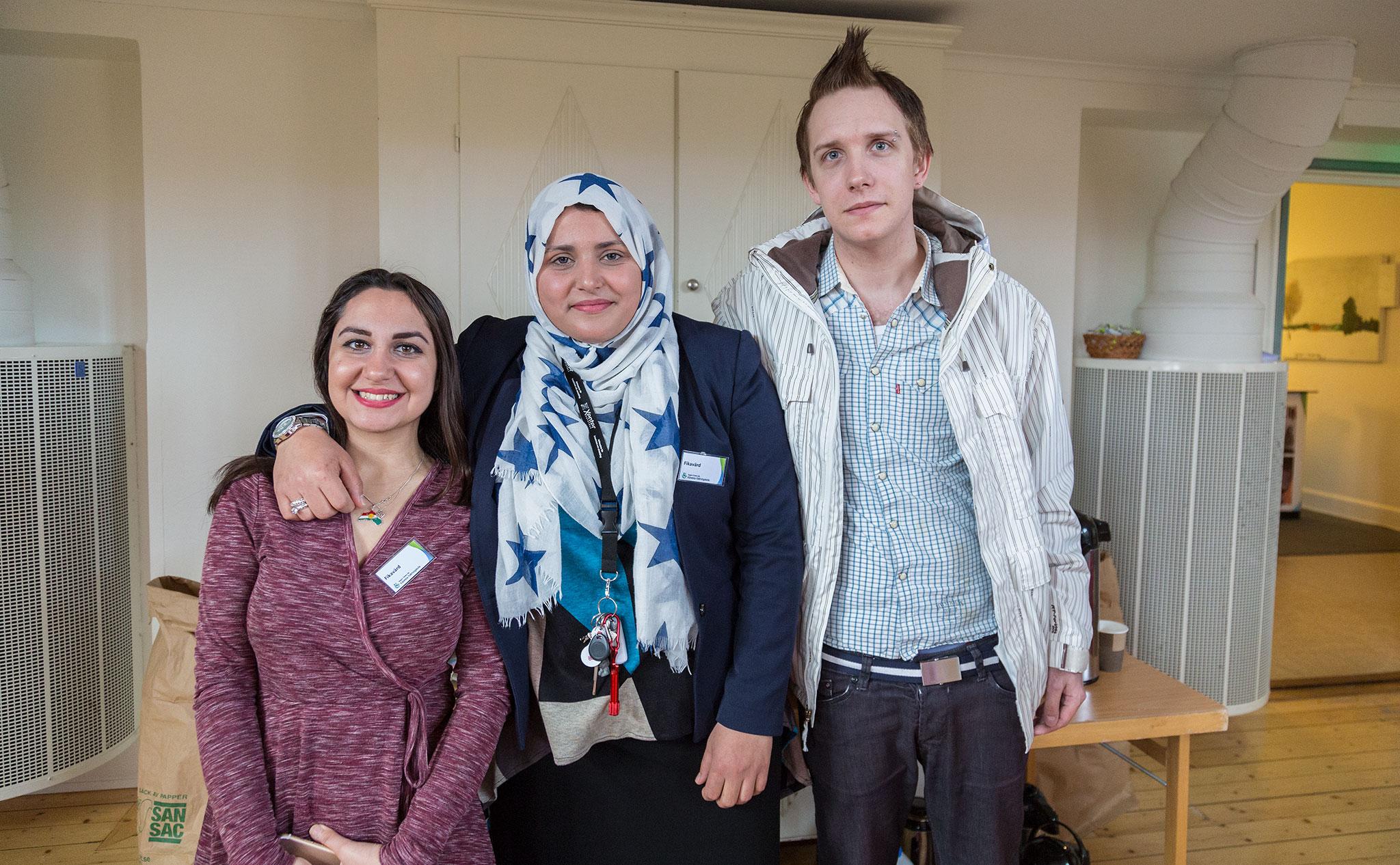 Tre deltagare står framför ett fikabord i aulan.