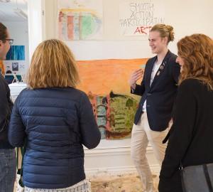 En deltagare visar sina verk för några besökare.