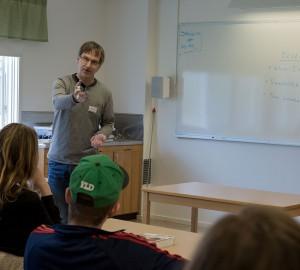 En lärare talar till en grupp sittande deltagare.