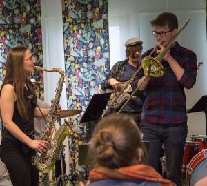 En saxofonist och en trombonist spelar mot varandra.