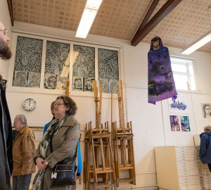 Ur en låg vinkel ser man hur en besökare tittar upp i taket i konstateljén och får syn på ett verk som hänger ifrån bjälkarna i taket - en jesus-liknande gestalt med brokig lila kappa.