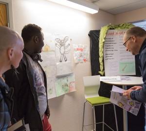 Flera besökare har samlats kring en deltagare som visar teckningar och sagor som allmän linje har gjort.