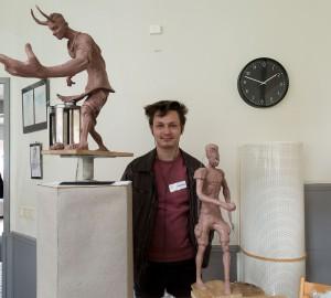 Andrius står mellan två stora ler-skulpturer.