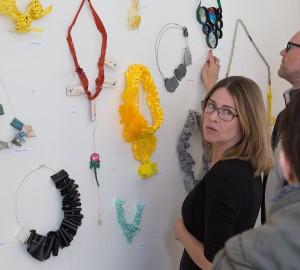 En deltagare visar smycken som hänger på en vägg.