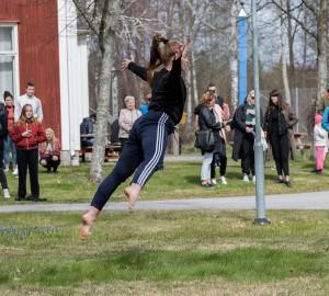 En dansare fångad mitt i ett hopp med ryggen mot kameran.