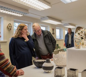 En grupp gamla och unga står och betraktar en keramikskulptur.
