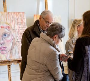 En grupp besökare står och pratar. Till vänster om dem syns en stor tavla med ett porträtt.