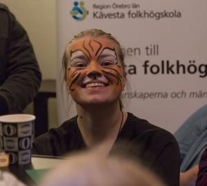 En deltagare med en orange ansiktsmålning tittar in i kameran och ler.