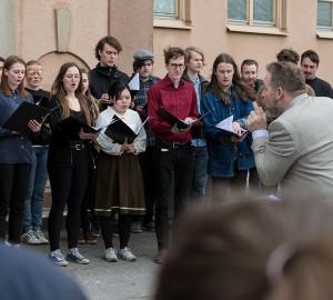 Kören står framför stora skolhuset, dirigent Stig Erik Nerman gestikulerar.