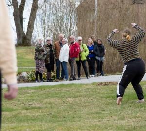 En dansare står i en pose på gräsmattan framför en grupp besökare som tittar på.