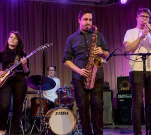 En gitarrist och två blåsare på scen.
