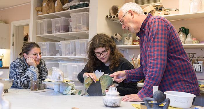 En deltagare diskuterar sin keramikskulptur med en lärare. De pekar båda på figuren. Bredvid sitter en till deltagare och tittar på.