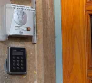 En porttelefon i silver som sitter bredvid dörren.