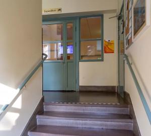 Ett trapphus, en kort trappa i förgrunden och en dörr i bakgrunden.
