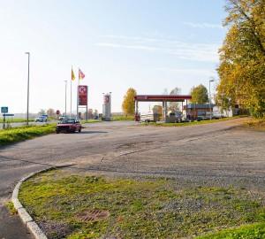En grusplan och en gångväg i förgrunden. I bakgrunden en bensinmack - Circle K.