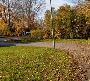 Gångvägen kröker sig åt vänster, i bakgrunden ser du en bilväg.