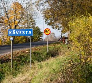 I förgrunden en blå vägskylt med texten Kävesta. Bakom den en röd och gul hastighetsskylt med texten 50.