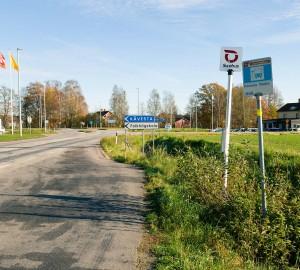 """En väggren med en skylt med texten """"Kävesta Västra"""". Långt till vänster kan man skymta en bensinmack."""