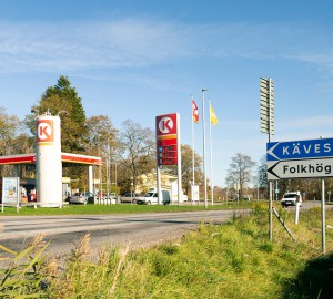 En vägskylt till höger med texten Kävesta Folkhögskola. På andra sidan vägen syns en bensinmack.