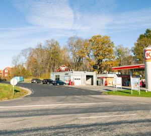 En väg korsar bilden från vänster till höger. En mindre väg löper rakt fram. Till höger en bensinmack.