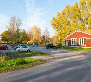 Vy över en stor parkeringsyta till vänster. Bredvid till höger ligger ett lågt rött hus - danshuset.