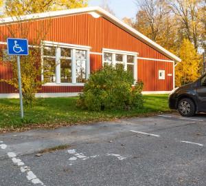 Låg vy över en parkeringsruta och en skylt med symbolen för handikapparkering. I bakgrunden ett lågt rött hus - danshuset.