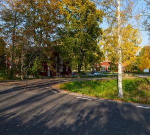 En väg som leder av in bland träd och röda hus.