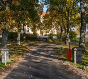 Vägen går in längs en mindre allé. I bakgrunden syns ett gult/orange hus - stora skolhuset.