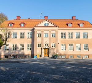 Stora skolhuset på håll - en tre våningar hög orange byggnad.