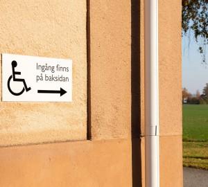En orange husgavel. En skylt med handikappsymbol är uppsatt på väggen.