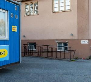 Till vänster en blå byggbarack. Lite längre bak syns en skylt med handikappsymbol på husväggen.