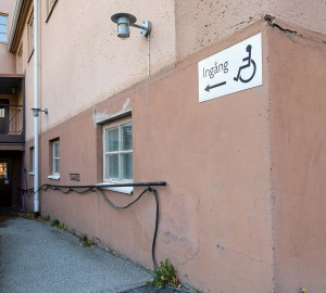Husgavel med skylt med handikappsymbol. Bakom den leder en ramp ner till en dörr.