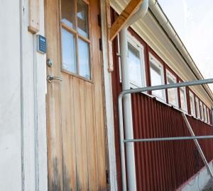 Konsthusets bakdörr fotad ur lågt perspektiv. Bredvid dörren en automatisk dörröppnare.