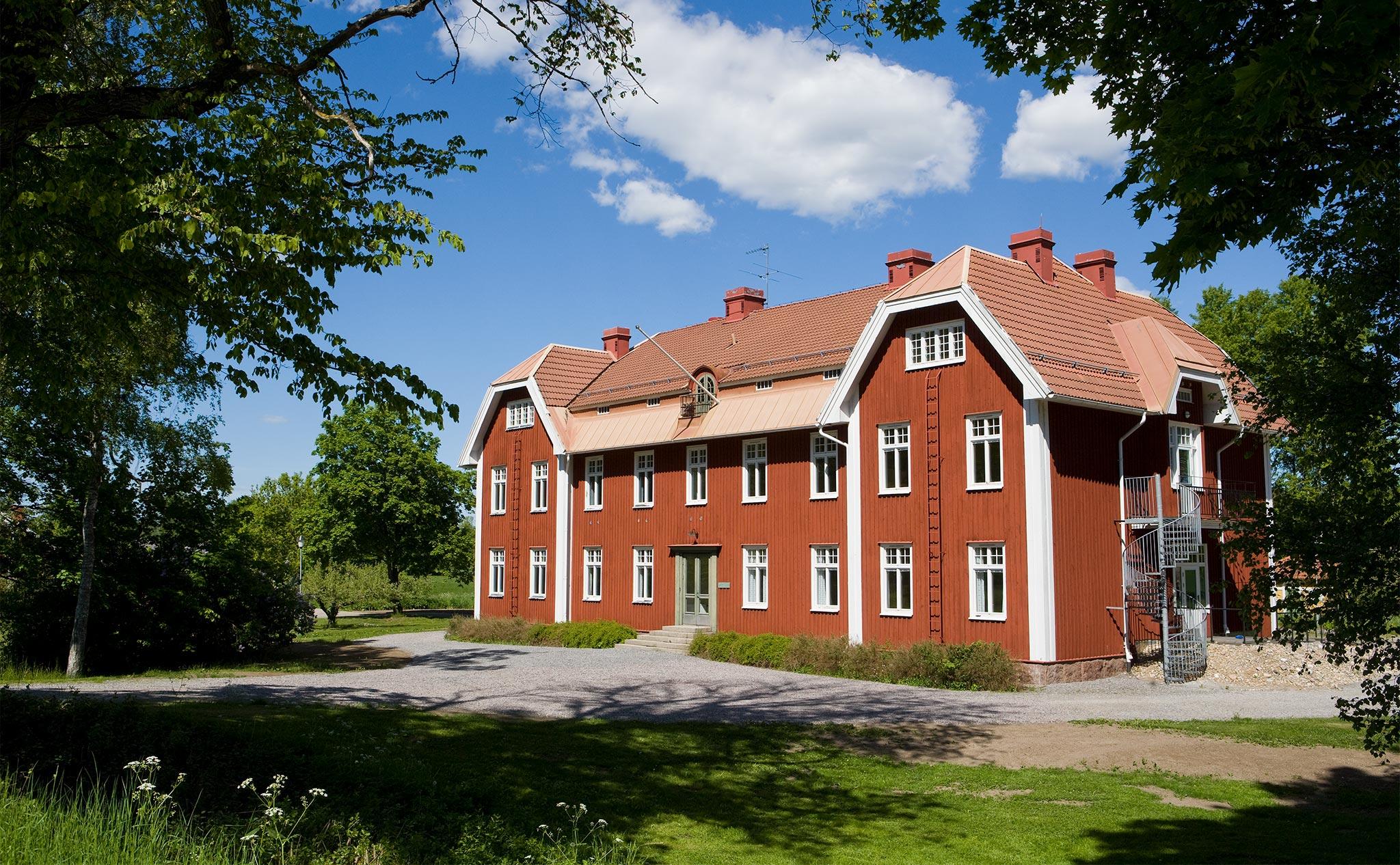 Ett stort rött hus med vita knutar i lantlig miljö.