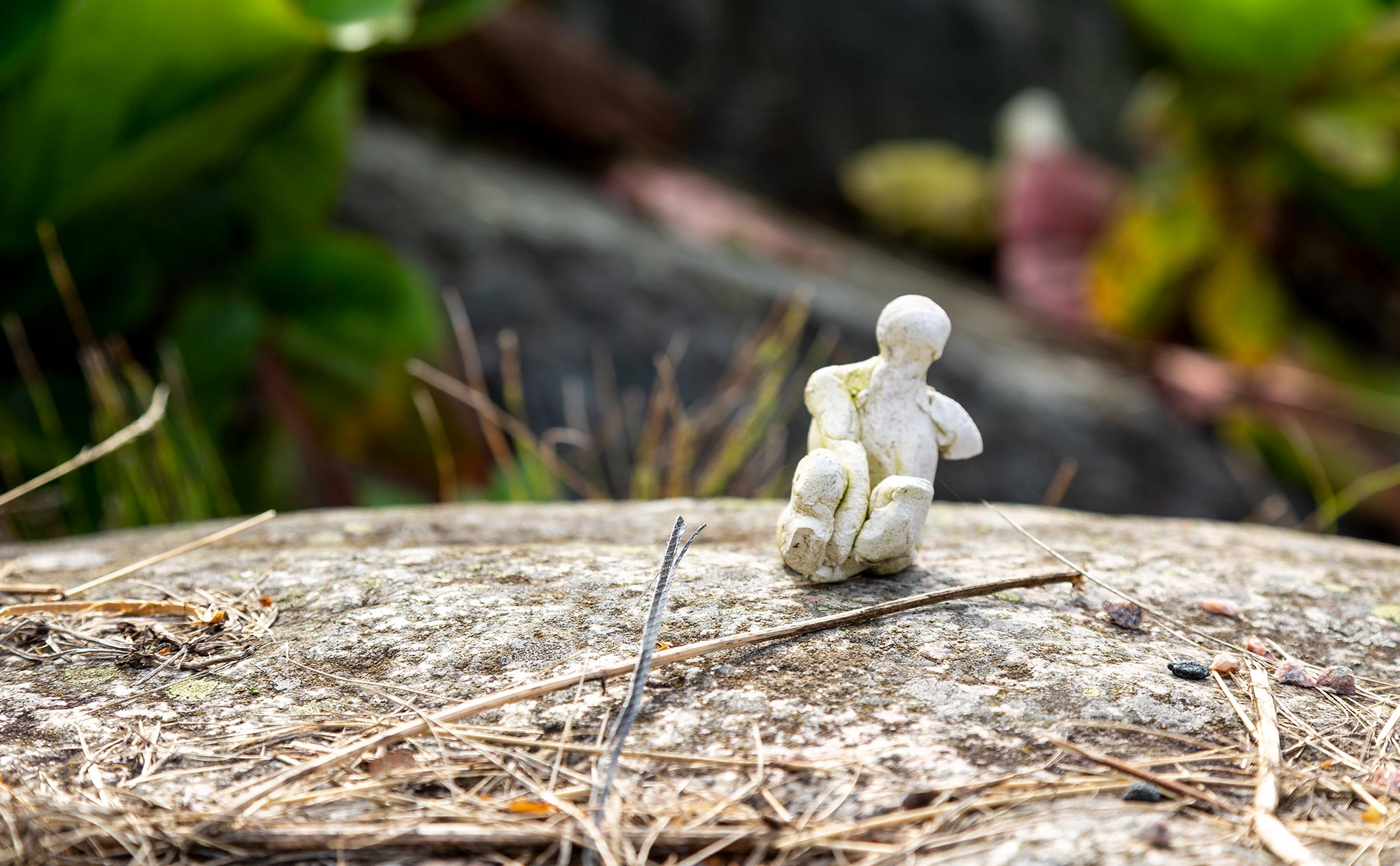 En liten vit keramikfigur i solen på en sten vid Kävestas damm.