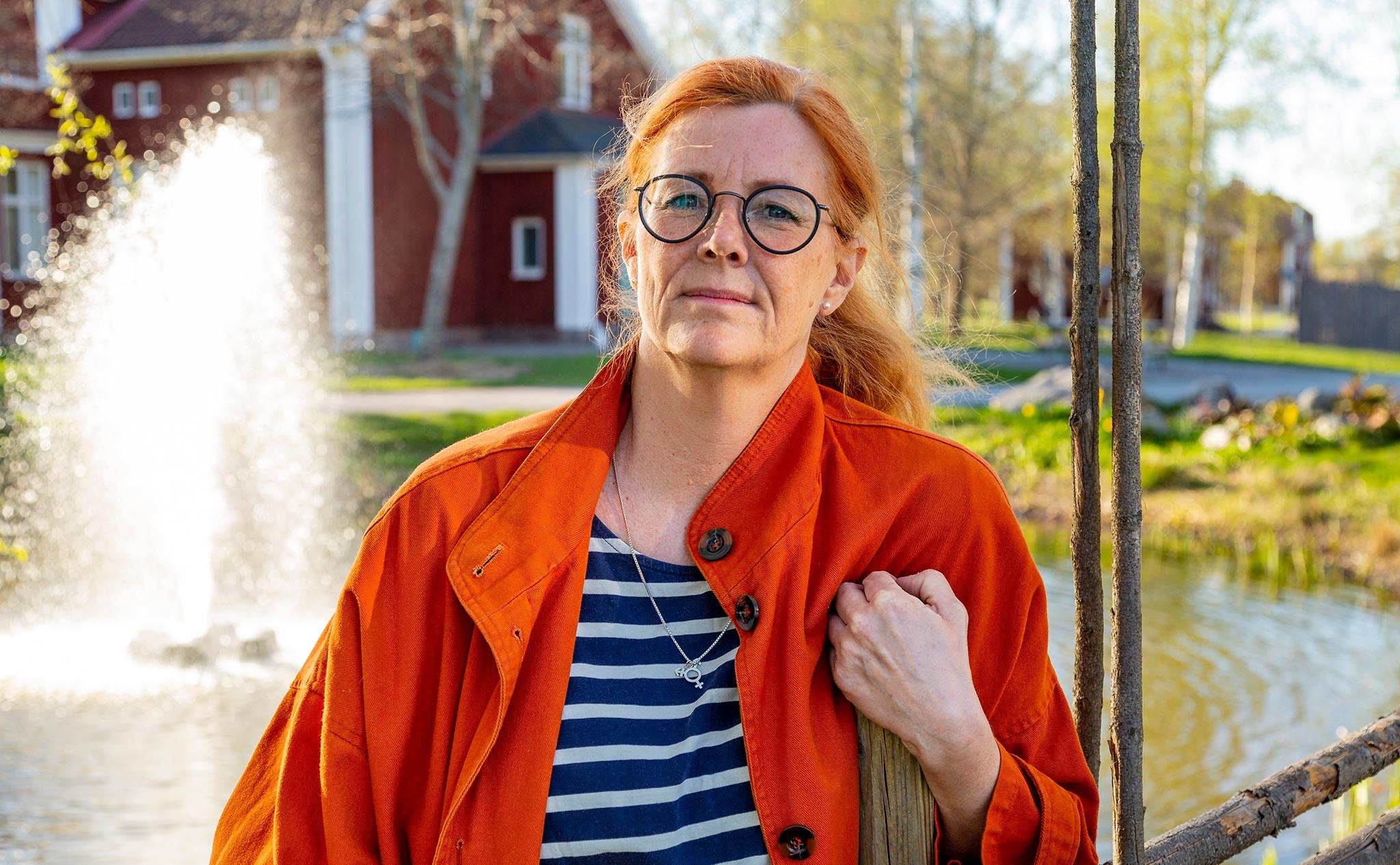 Skolans rektor Lisa lutar sig mot en gärdesgård, framför en damm med fontän.