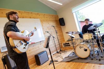 En gitarrist och en trummis spelar tillsammans i ett ljust övningsrum.