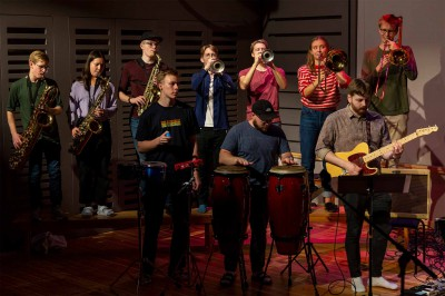 En sju personer stark blåssektion spelar bakom en percussion-sektion och en gitarrist.