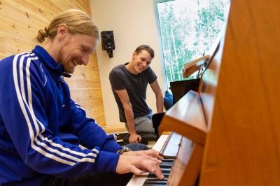 En lärare visar hur man spelar något på piano. Läraren och deltagaren skrattar.