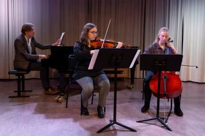 En trio på piano, fiol och cello spelar kammarmusik.