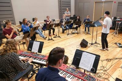 En stor grupp deltagare övar tillsammans: sju blåsare, två pianister och en sångare syns i bild.