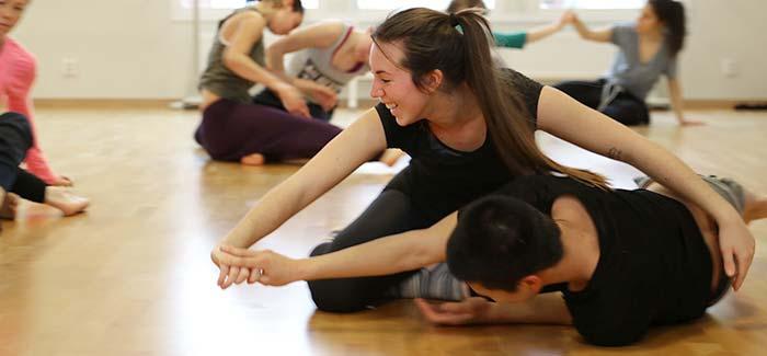 Två dansare skrattar på golvet under en workshop.
