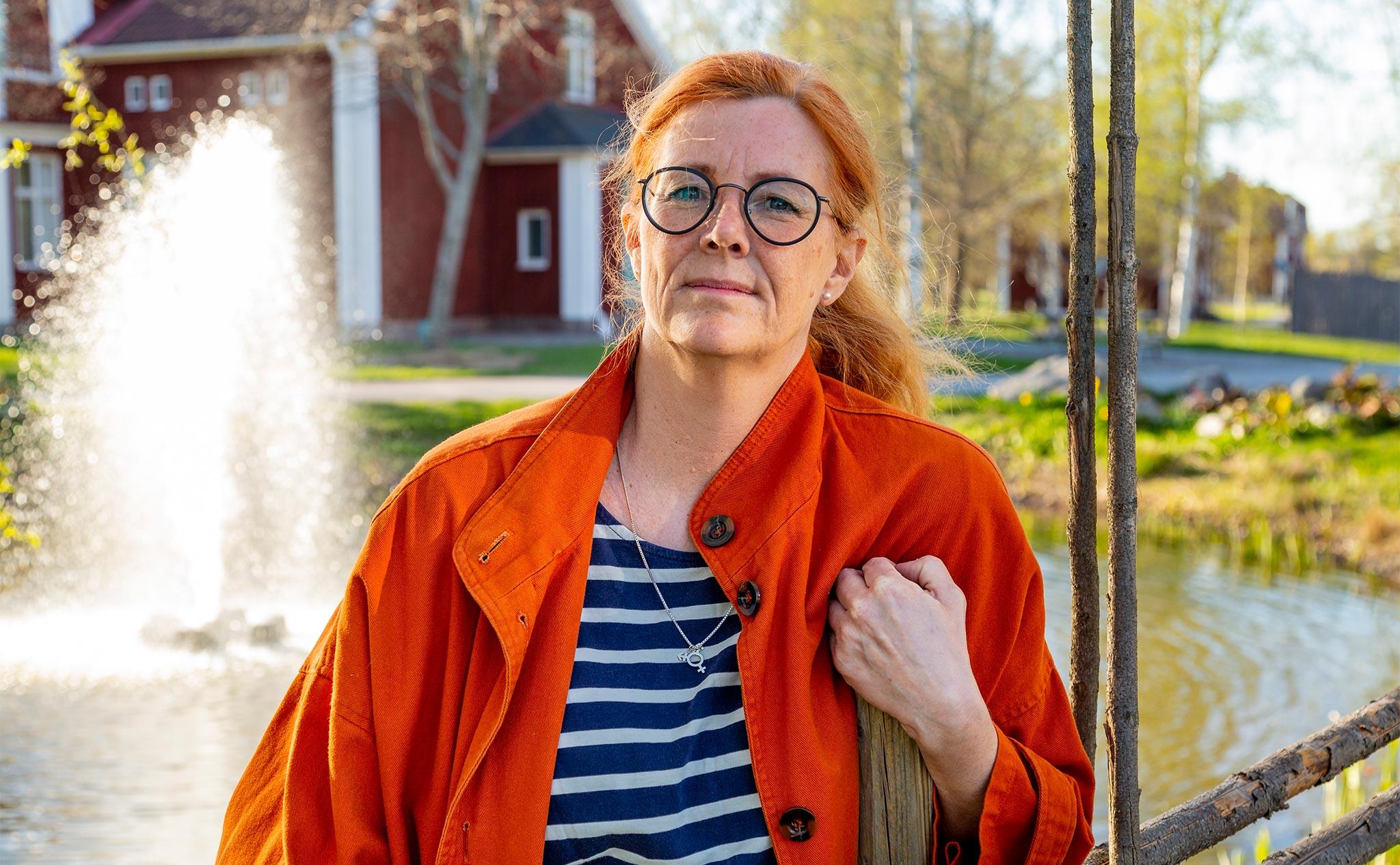 Rektor Lisa Rosander lutar sig mot en gärdesgård.