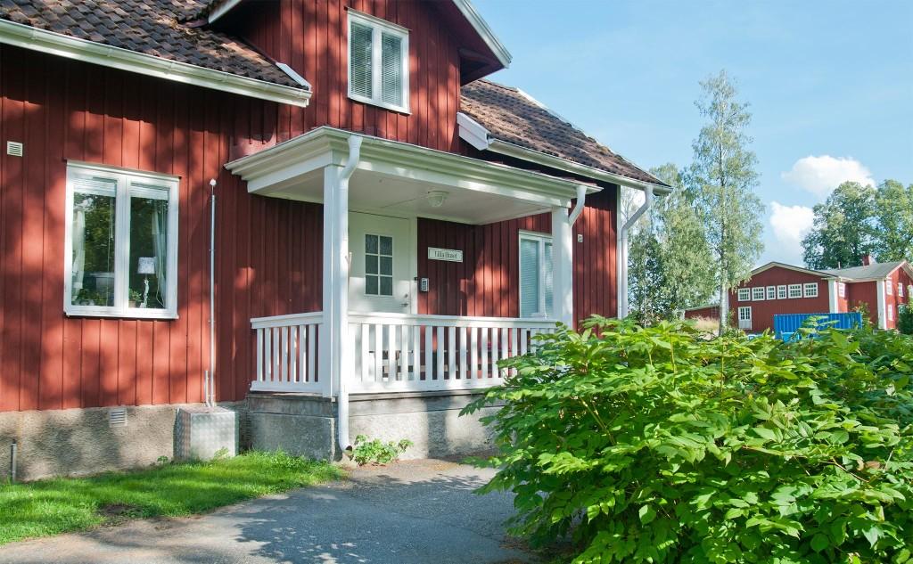 Ett rött hus med vitmålad veranda.