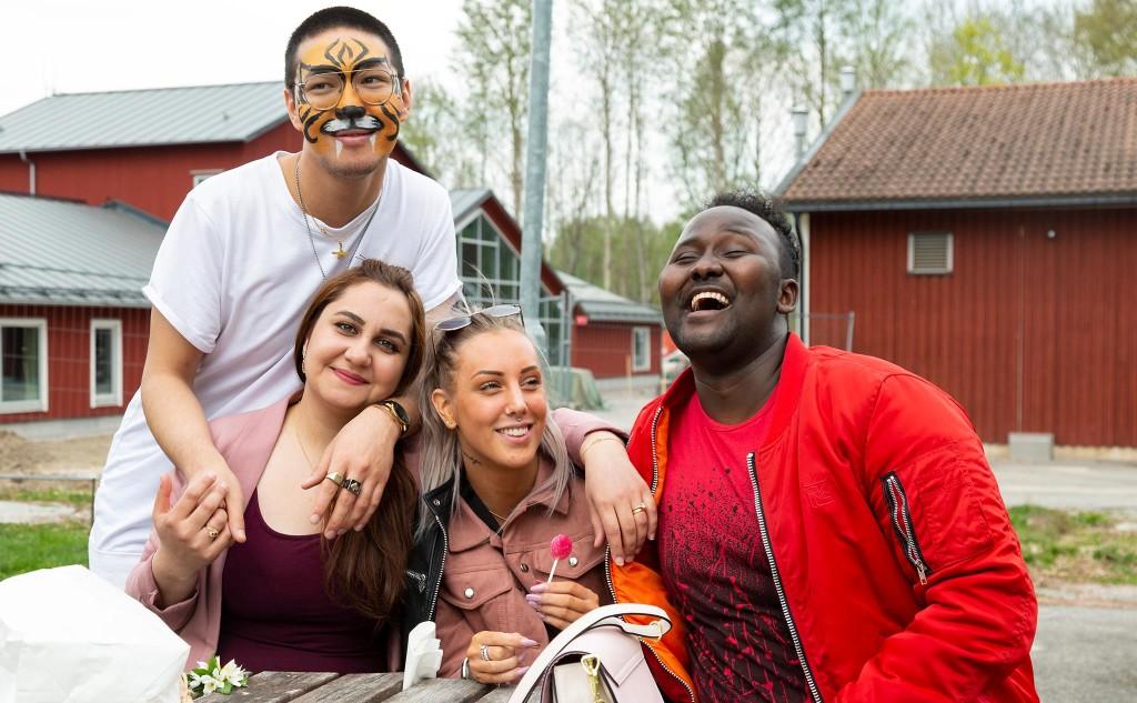 Fyra glada deltagare skrattar och tittar in i kameran.